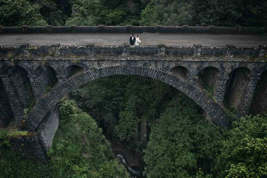 Just-married couple on old bridge
