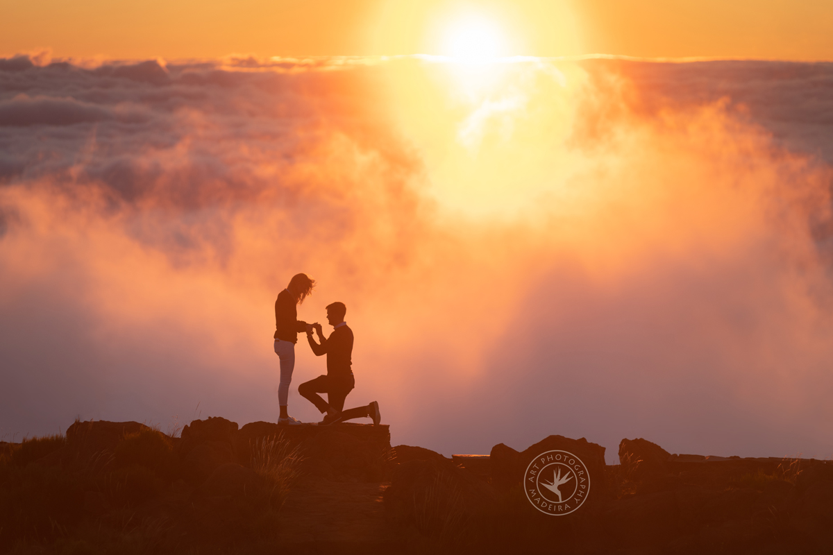 Man puts a ring on woman's finger at sunrise