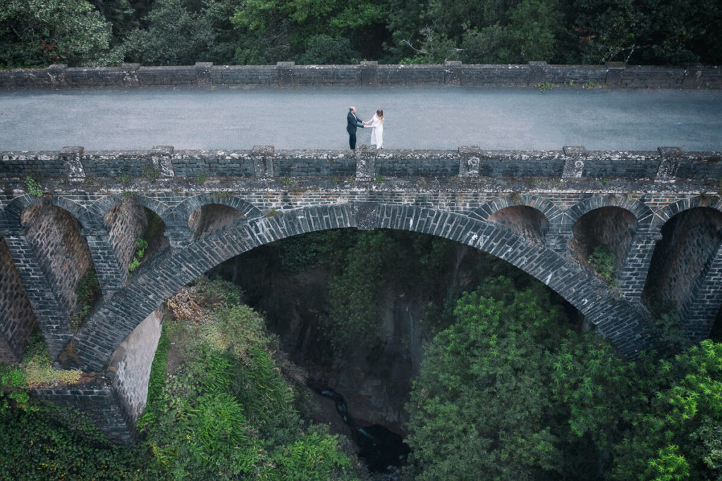 Just-married couple on old bridge