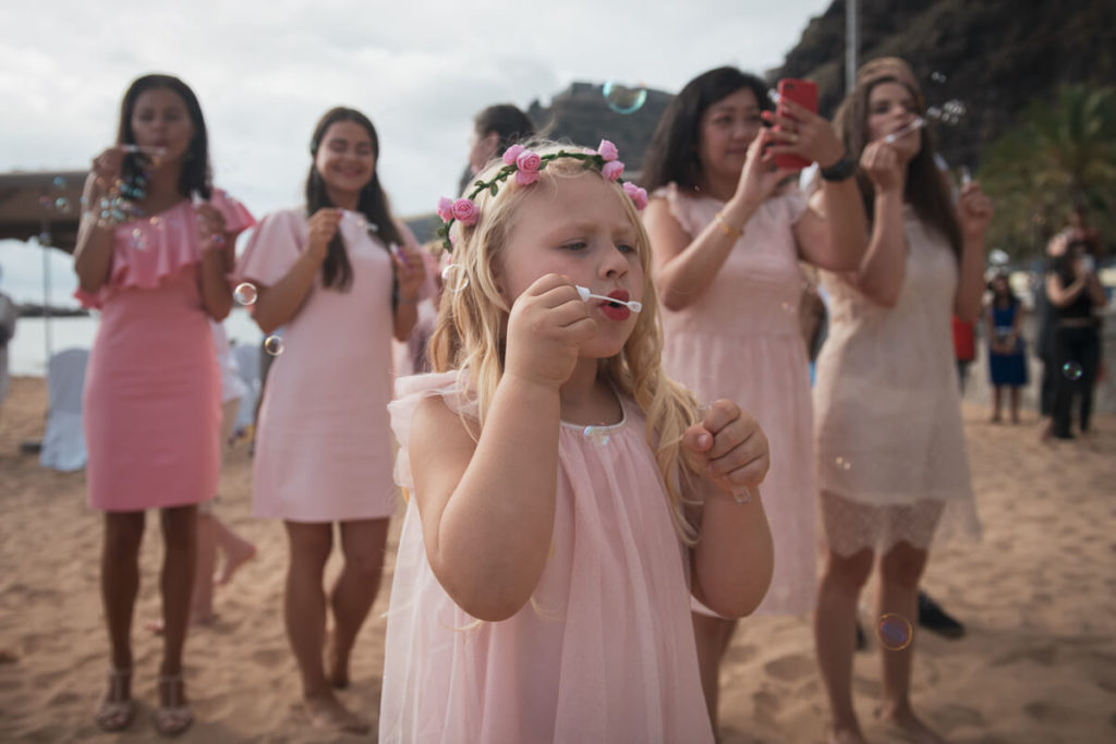 kids blowing bubbles at beach wedding ceremony