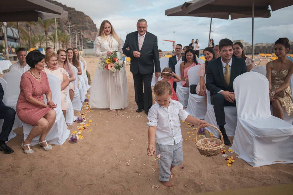 father takes a bride to wedding ceremony at the beach